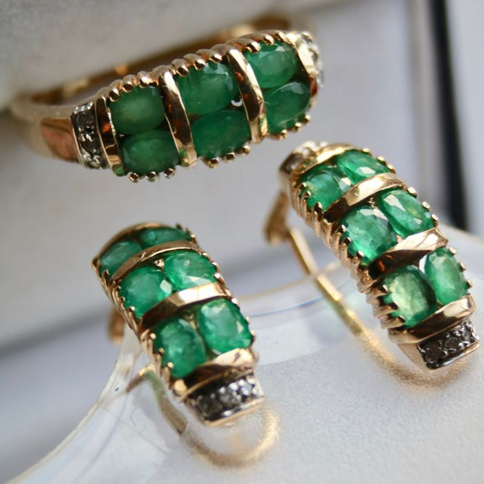 Vintage set: White/yellow gold Ring and pair of Earrings with Omega locks set with oval faceted Emeralds approx. 3Ct total and 18 small octagonal diamonds