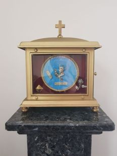 Copper reliquary with 4 relics on red velvet behind bevelled glass