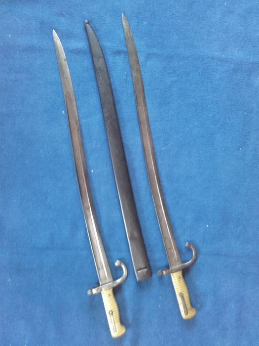 "Lot with 2 Yatagan Bayonets for Chassepot Rifle, with sheath First piece: manufacturer's hallmark "" ... St. Etienne... 1869 "", second Piece from 1875 without manufacturer's mark, with slide-in plate and screws, belt mounting available, cleaned original steel sheath with Carrying handle, troop stamp"