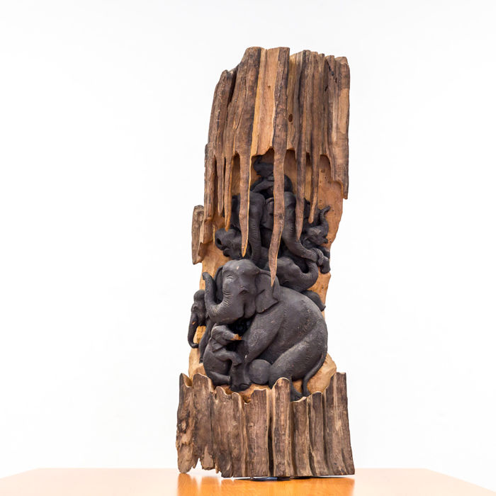 A driftwood with a semi-relief of elephants in a cave