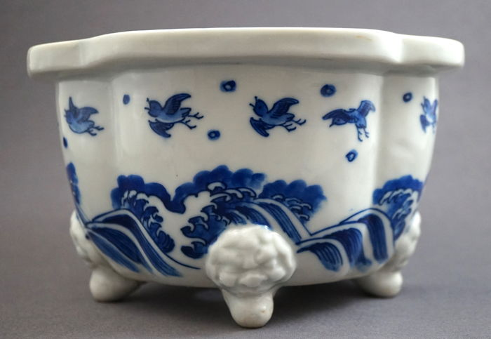Beautiful contoured flowerpot decorated with many flying birds above a turbulent sea, at the top there are geometrical and swastika patterns with Buddhist items - Japan - 19th century