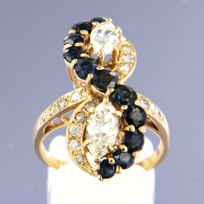 18 kt yellow gold ring with 2 marquise cut diamonds, 1.20 carat, and 18 brilliant cut diamonds, 0.50 carat, and 11 brilliant cut sapphires, 1.50 carat, ring size 54 (17.25)