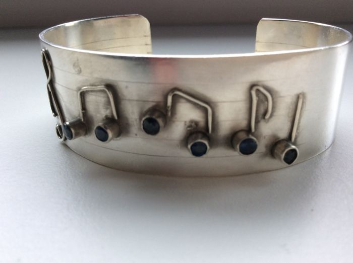 A unique silver cuff decorated with musical notes and sapphires