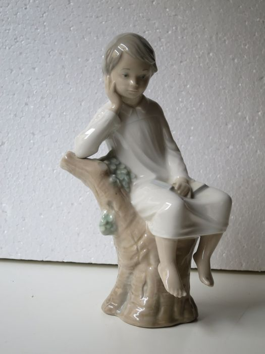 Lladro porcelain figure - Small Boy in night shirt sitting with book.