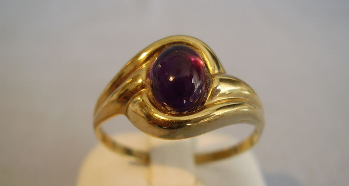 Golden ring with oval vivid, natural amethyst cabochon of 1.5 ct