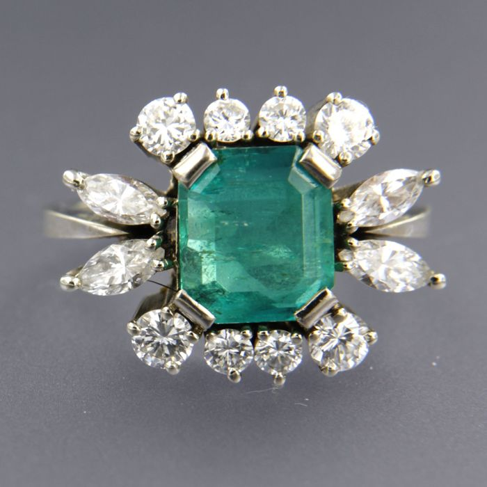 18 k white gold ring with an emerald cut emerald in the centre (total 2.00 carat) and an entourage of marquise and brilliant cut diamonds total approx. 1.10 carat