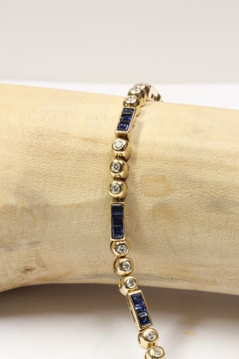 14 kt Yellow gold bracelet set with brilliant cut diamond and blue sapphire.