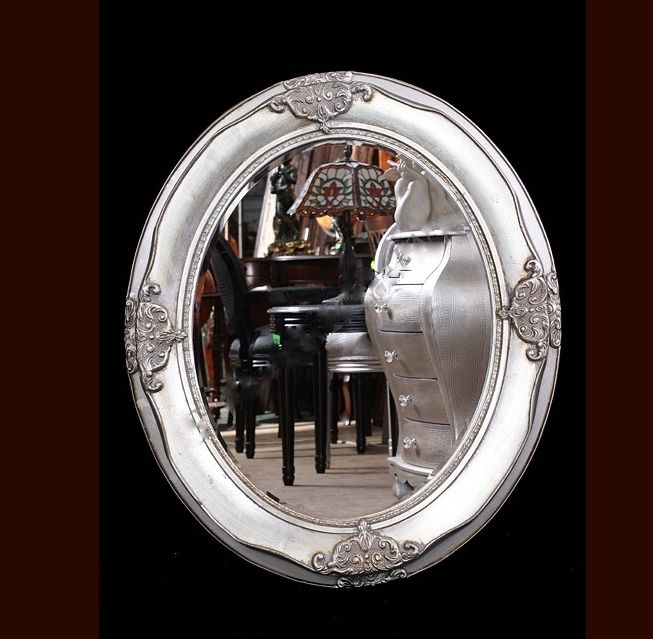 A large mirror in a hand-made, silver, wooden frame.
