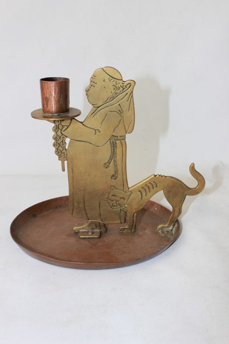Yellow and red-copper candlestick in the form of a monk and a cat