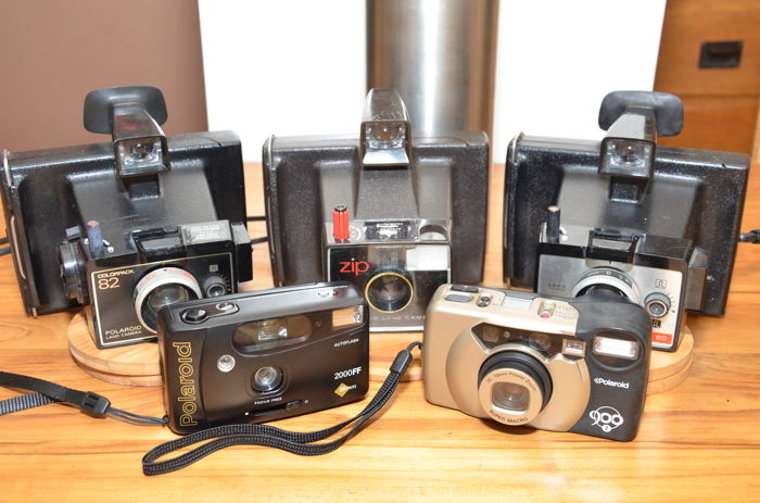 Five Polaroid cameras, including three instant and two 35 mm compact cameras