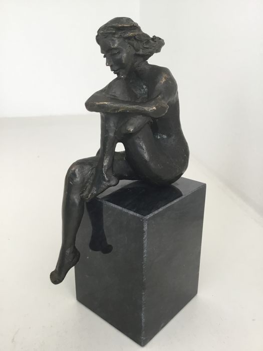 Bronze plated sculpture of a seated woman