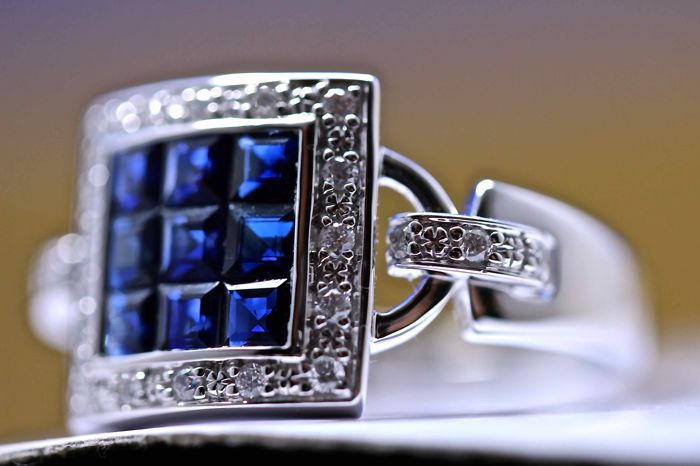Ring in 18 kt white gold, with 9 princess-cut sapphires in the centre (1.29 ct in total), surrounded by 22 natural brilliant-cut diamonds (0.15 ct in total)