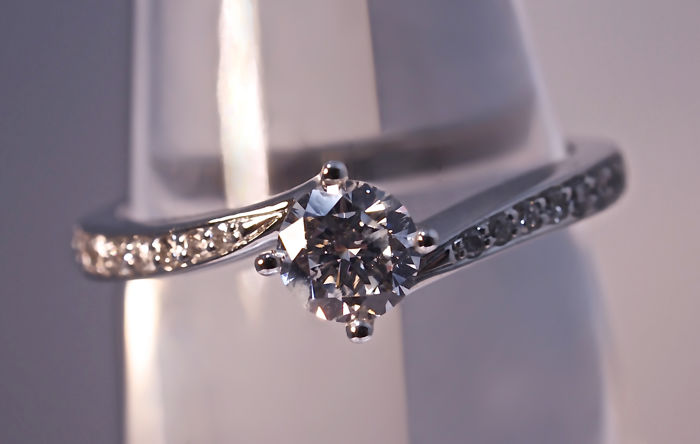 Modern 18 kt white gold solitaire ring with a central brilliant-cut diamond of 0.33 ct and 2 rows of 8 diamonds each, cut in decreasing sizes, 0.14 ct in total