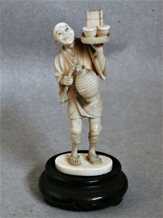A very fine single piece ivory okimono of a person with a tray and a lantern - Japan - ca 1890 - 1900 (Meiji period)
