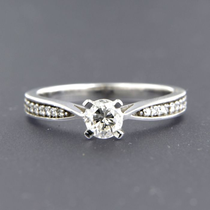 14 kt white gold solitaire ring centrally set with a brilliant cut diamond and 16 side stones, brilliant cut diamonds of approx. 0.65 in total