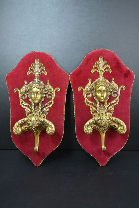 Two bronze coat hooks with a red velvet backing