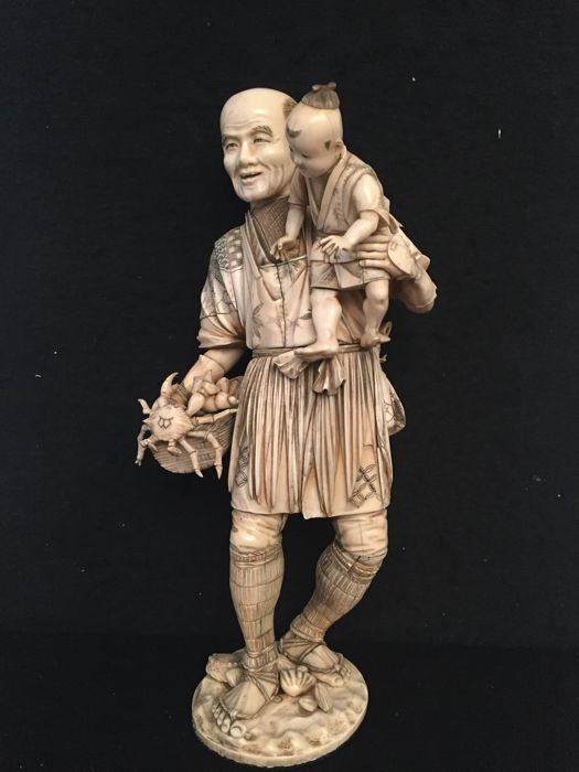 Large ivory okimono depicting a fisherman with child (41 cm), with maker's, red lacquer - Japan - 1868-1912 (Meiji period)
