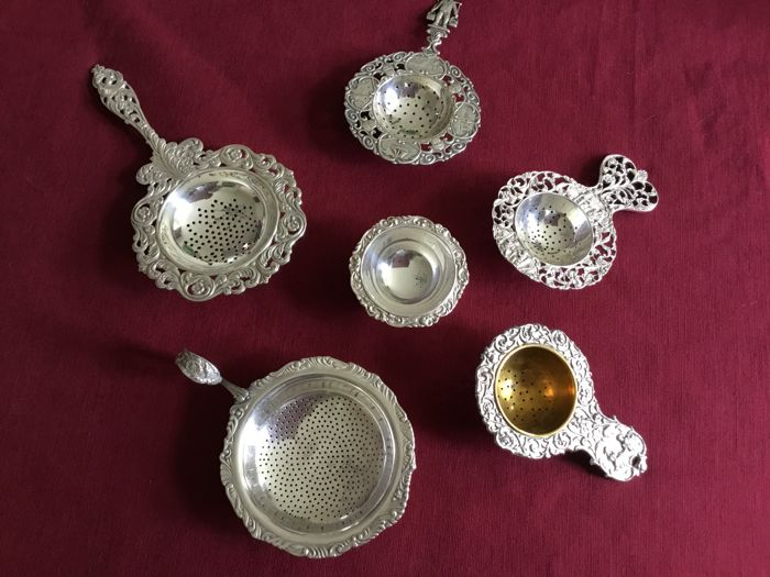5 silver plated tea sieves with beautifully decorated scenes and drip tray