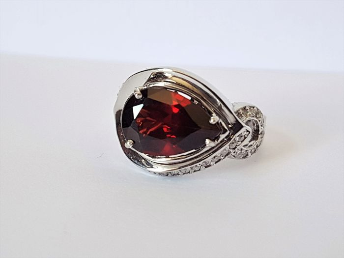 18 kt Women's ring, 5.8 g, in white gold with garnet, 3.10 ct, and diamonds, 0.30 ct, size: 55.5