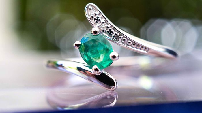 Ring18 kt white gold with an oval emerald of 0.447 ct, certified, ring shank includes one row of natural brilliant-cut, pave-set diamonds for a total of 0.02 ct.