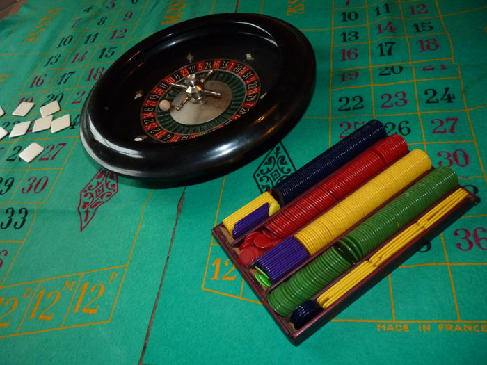 Retro black bakelite table roulette wheel + early plastic counters/chips.