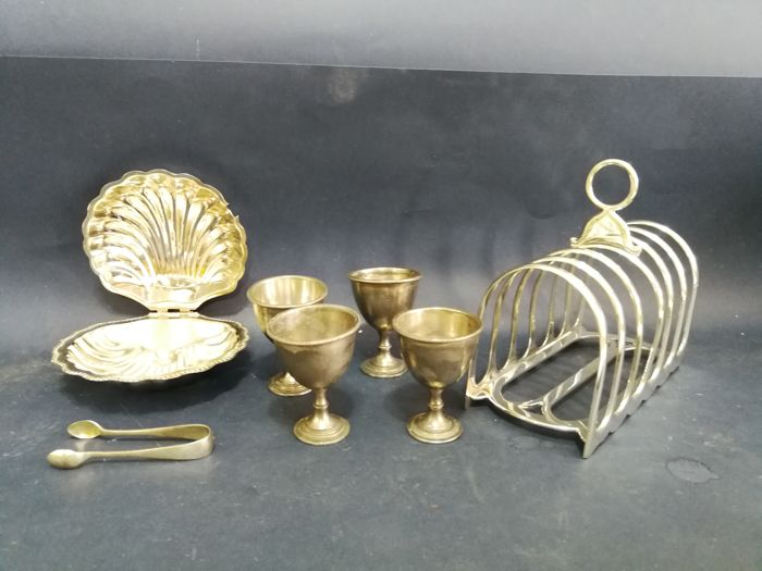Silver plated toast track with Gothic arch, shell tray, cooking tongs and 4 egg cups