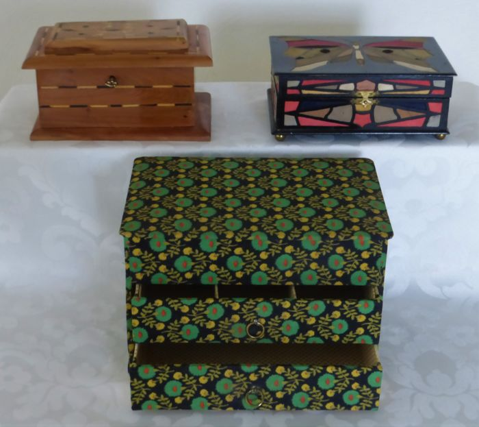Three jewellery boxes - one is inlaid with patterns and butterfly of silk - one walnut box with motifs - one chest of drawers upholstered with fabric