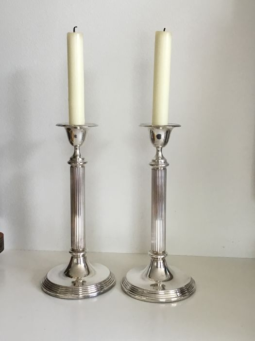 Two silver plated candle stands with ribbed handle and rim along the base