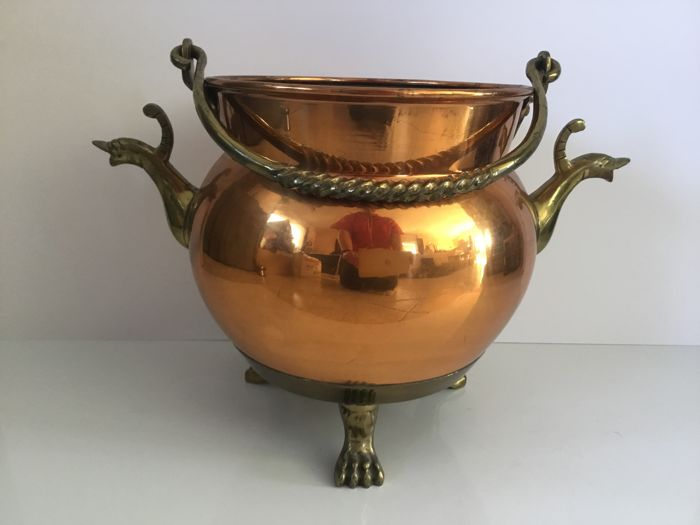Copper cache-pot on feet with claws gracefully twisted handle and sides containing animal figures