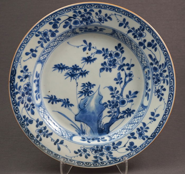 Flat porcelain plate with a decoration of blossom and bamboo branches on a rock formation - China - c. 1740, early Qianlong period (1735–1796)