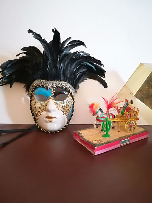 Two characteristic Italian objects - Venetian mask and Sicilian cart
