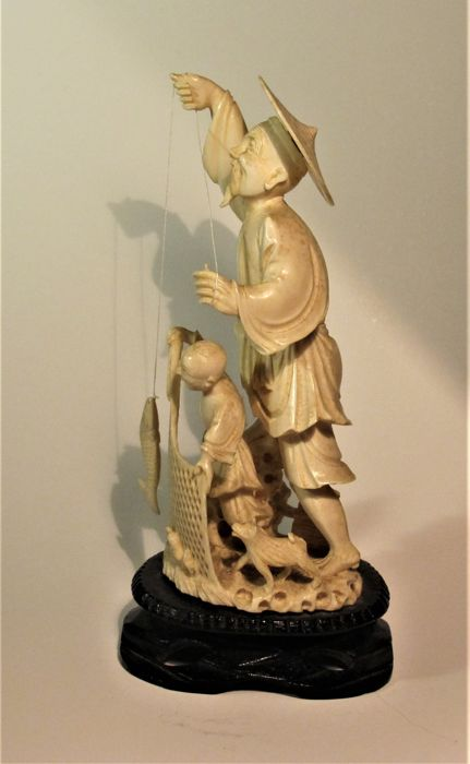 Ivory okimono, depicting a fisherman with a child and dog - China - Circa 1900/30
