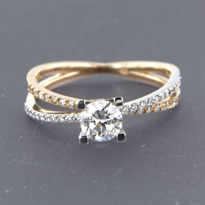 14 kt bi-colour gold solitaire ring set with a central brilliant cut diamond of 0.57 carat and 38 brilliant cut diamonds of 0.13 carat