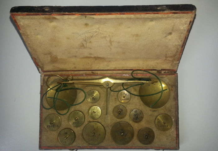 Coin weight scale with weights in a lined box with decorations