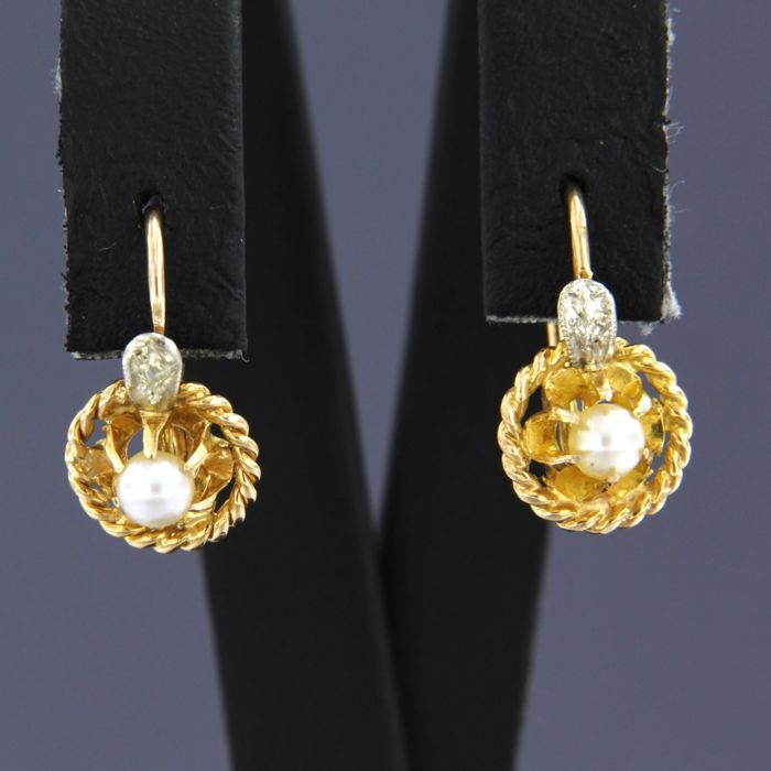 14 kt bicolour gold dangle earrings set with a cultured freshwater pearl