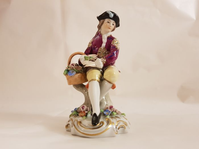 Capodimonte (Naples) - polychrome porcelain figure depicting a sitting young gentleman with basket of fruit