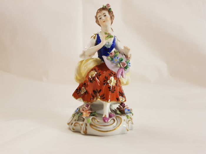 Capodimonte (Naples) – polychrome porcelain figure depicting a young lady sitting with floral hat.