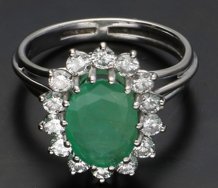 18 kt - White gold ring with emerald with a diameter of 7 x 9 mm, around the emerald 13x brilliant cut diamonds, each of 0.07 ct - Ring size 17.25 mm