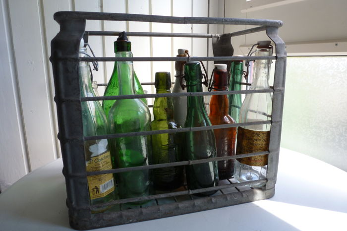 A zinc-plated crate with 13 old bottles of various brands - mid 20th century - various countries