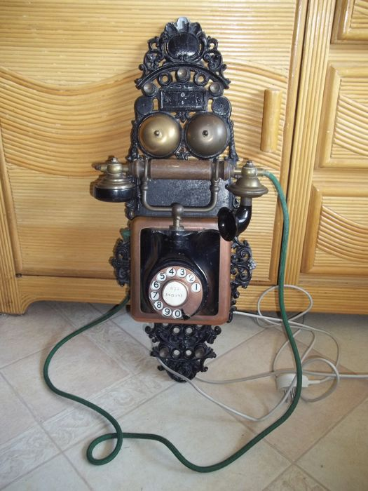 Antique bakelite and brass wall telephone on cast iron back plate
