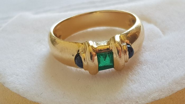 18 kt gold ring with an emerald and sapphires. Ring size: 54