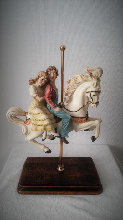 A boy and a girl riding om a carousel horse - 2nd half of the 20th century - by the Italian sculptor Ennio Furiesi