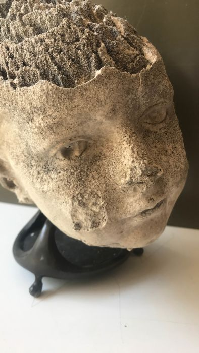 A special stone head affected by nature on bronze foot