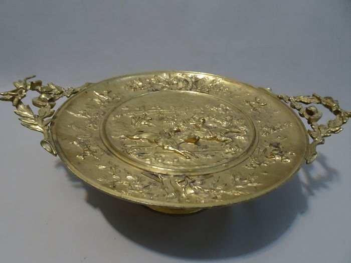 Brass bowl on a stand with a hunting scene and relief