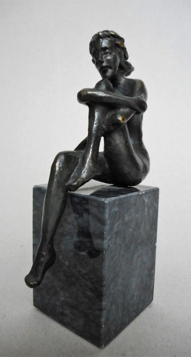 Bronzed sculpture of a naked sitting woman