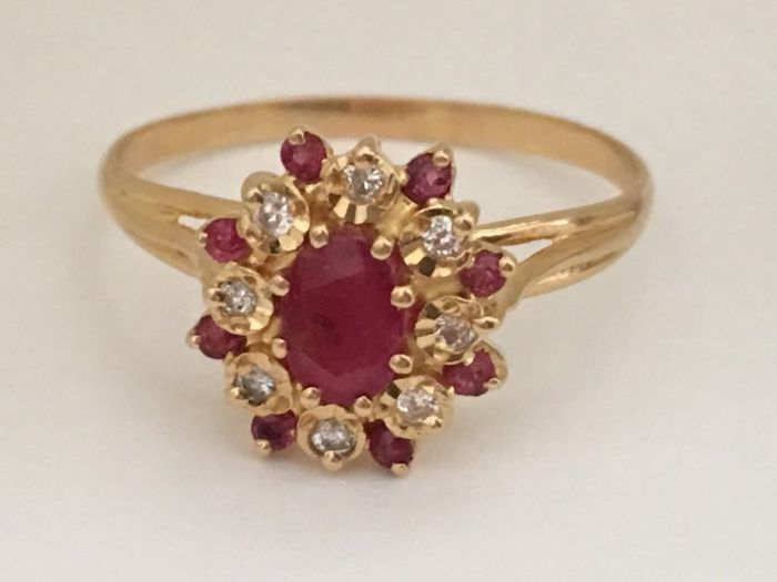 Cocktail ring rosette of yellow gold of 18 kt/750 with central oval cut ruby of 0.64 ct - 8 Round cut rubies of 0.28 ct - 6 Brilliant cut diamonds of 0.24 ct - Ring diameter 20 mm - Weight 3.350 g
