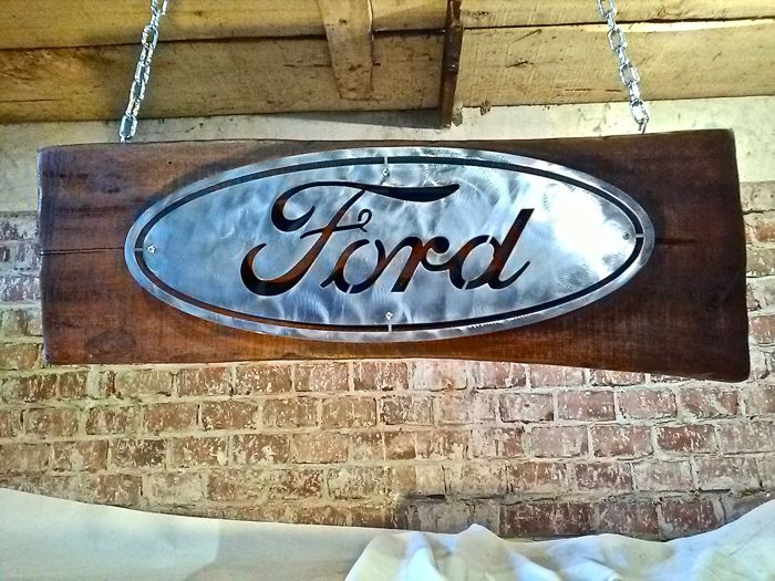 Large sized Ford sign, oval iron on a wooden panel