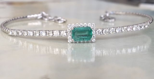 Magnificant 18 kt white gold women's bangle set with brilliant cut diamonds approx. 0.70 ct G/VS/SI and an emerald approx. 0.60 ct