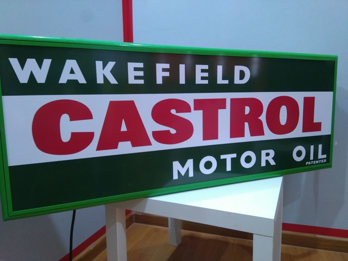 Large luminous sign of CASTROL WAKEFIELD MOTOR OIL.