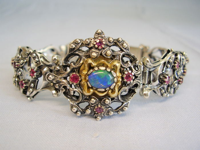 Antique bracelet / watch with floral design adorned with round faceted rubies (1 ct) and opal (3 ct) in gold-plated socket